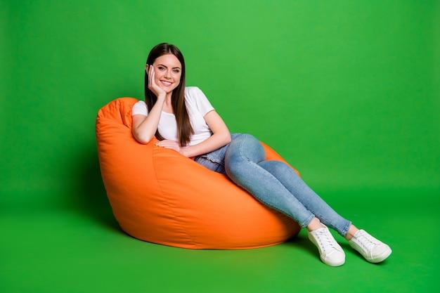 Zdjęcie ładnej ślicznej brunetki włosy młoda kobieta ręka policzek sukienka biała koszulka dżinsy obuwie siedzieć na pufie na białym tle na zielonym tle