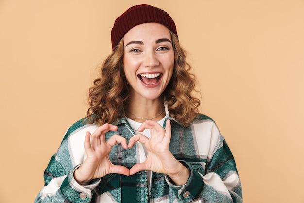 Zdjęcie ładnej, zabawnej kobiety w czapce z dzianiny, uśmiechniętej i gestykulującej sercem na beżowym tle