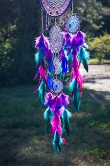 Zdjęcie łapacza snów wykonane ręcznie, przy użyciu nici, koralików i piór koguta