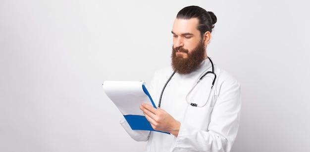 Zdjęcie lekarza mężczyzny w mundurze robiącego notatki na kartkach papieru