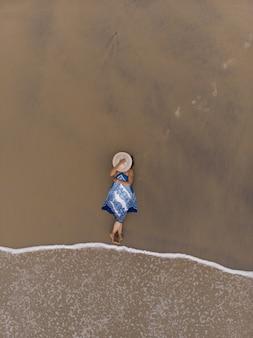 Zdjęcie lotnicze azjatyckiej kobiety leżącej na piaszczystej plaży