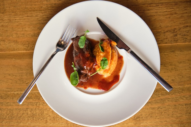 Zdjęcie lotnicze dania z policzków cielęcych z kokosowym mojo i puree z tuńczyka z sosem pomarańczowym podane w białym talerzu ceramicznym z nożem i widelcem na drewnianym stole