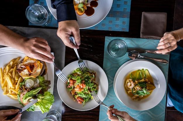 Zdjęcie lotnicze ludzi dzielących się surowym jedzeniem na drewnianym stole