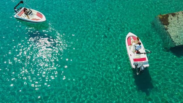 Zdjęcie lotnicze ludzi jeżdżących motorówkami na przezroczystym morzu