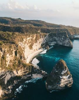 Zdjęcie lotnicze oceanu otoczonego wysokimi górami pokrytymi zielenią