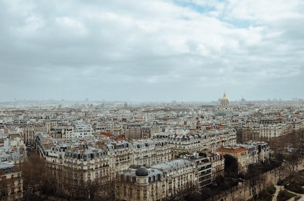 Zdjęcie lotnicze paryża pokrytego zielenią i budynkami pod zachmurzonym niebem we francji