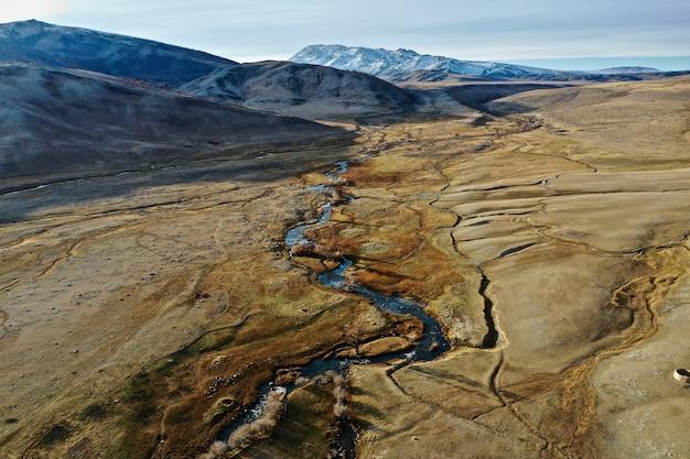 Zdjęcie lotnicze rzeki na dużej suchej murawie