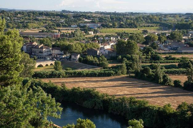 Zdjęcie lotnicze wsi otoczonej polami i rzeką. narbonne we francji
