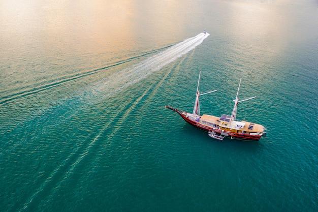 Zdjęcie lotnicze z drona łodzi żaglowej zadokowanej w tropikalnej zatoce śródziemnomorskiej z krystalicznie czystym turkusowym morzem