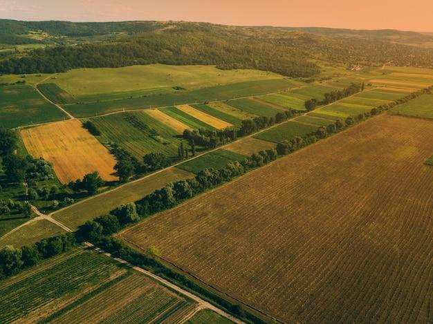 Zdjęcie lotnicze z drona z pięknym krajobrazem farmlamnd o zachodzie słońca w wiejskiej atmosferze