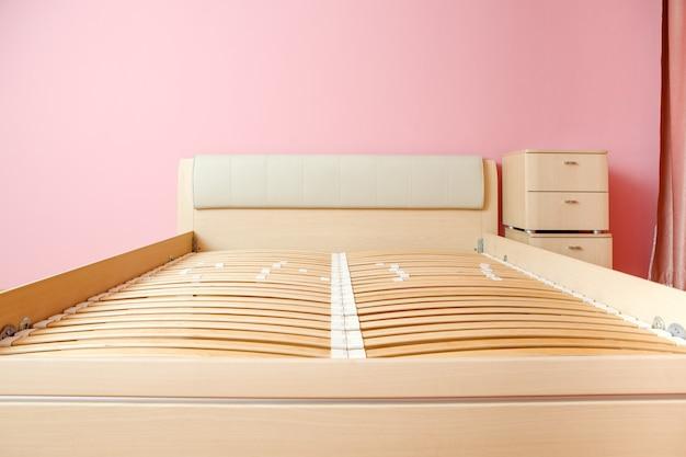 Zdjęcie łóżka bez materaca, komoda w pokoju