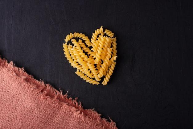 Zdjęcie makaronu na ciemnym stole w formie serca, i love pasta