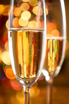 Zdjęcie makro dwóch kieliszków do szampana zastrzelonych przed błyszczącymi lampkami choinkowymi