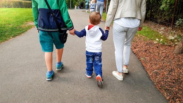 Zdjęcie małego chłopca trzymającego matkę i starszego brata za rękę i spacerującego po jesiennym parku