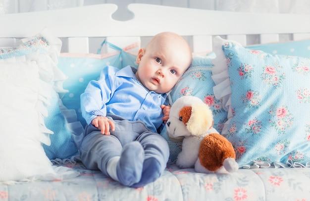Zdjęcie małego chłopca w niebieskim ubraniu, siedząc na kanapie