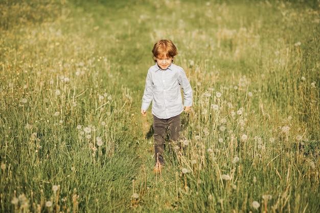 Zdjęcie małego rudowłosego chłopca w wieku 3 lat biega po kwitnącej łące, dziecko spaceruje na świeżym powietrzu