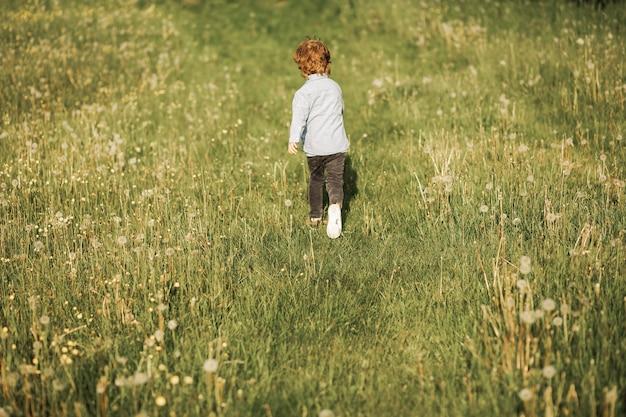 Zdjęcie małego rudowłosego chłopca w wieku 3 lat, który biega, dziecko chodzi na świeżym powietrzu, zdjęcie z tyłu