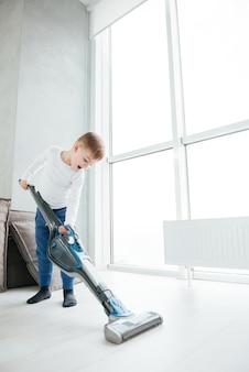 Zdjęcie małego wesołego chłopca sprzątanie domu. spójrz na podłogę.