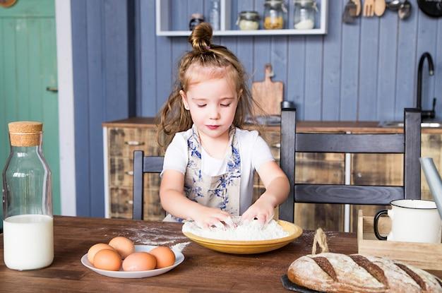Zdjęcie małej dziewczynki sama gotuje w kuchni