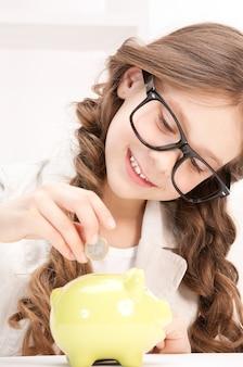 Zdjęcie małej dziewczynki ze skarbonką i monetą