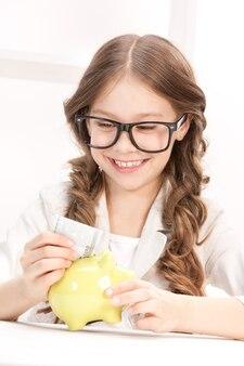 Zdjęcie małej dziewczynki ze skarbonką i pieniędzmi
