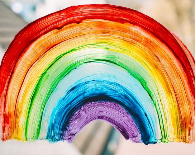 Zdjęcie malującej tęczy na oknie tęcza malowana farbami na szkle