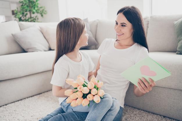 Zdjęcie mamy dziecko daje kobietę prezenty na dzień kobiet bukiet róż pocztówka w domu w pomieszczeniu