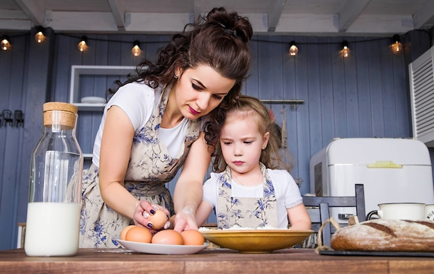 Zdjęcie mamy i córki gotuje się razem z mąki, jajek i mleka