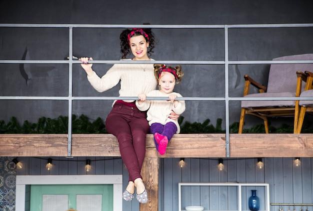 Zdjęcie mamy i córki siedzą na drugim piętrze domu