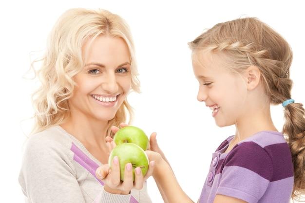 Zdjęcie mamy i małej dziewczynki z zielonym jabłkiem (skup się na dziewczynce)