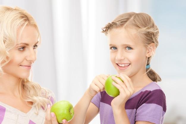 Zdjęcie mamy i małej dziewczynki z zielonym jabłkiem