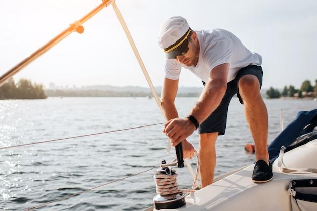 Zdjęcie marynarza stoi na jachcie i kręci wokół liny. jest spokojny i skoncentrowany. młody człowiek ciężko pracuje. przygotowuje się do żeglugi.