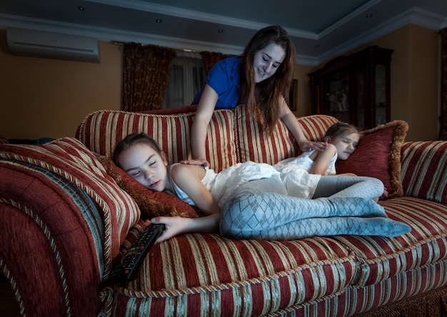 Zdjęcie matki budzącej dwie córki zasnęła w nocy podczas oglądania telewizji