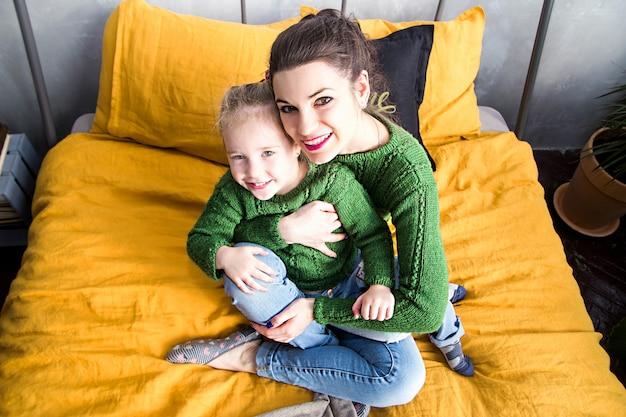 Zdjęcie matki i córki leżą razem na żółtym łóżku