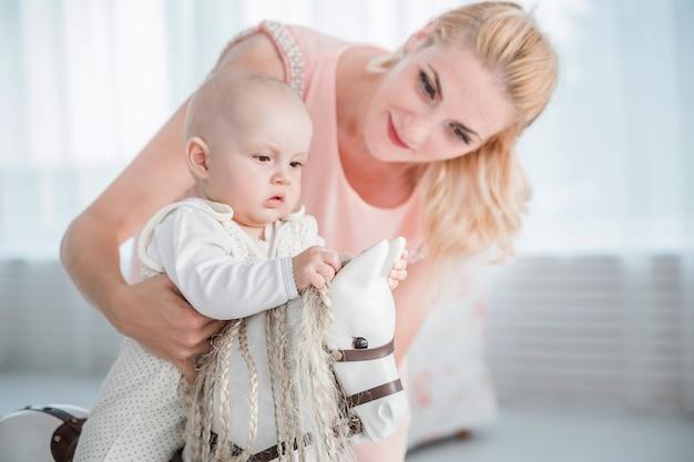 Zdjęcie matki toczy jej synka na koniku zabawka