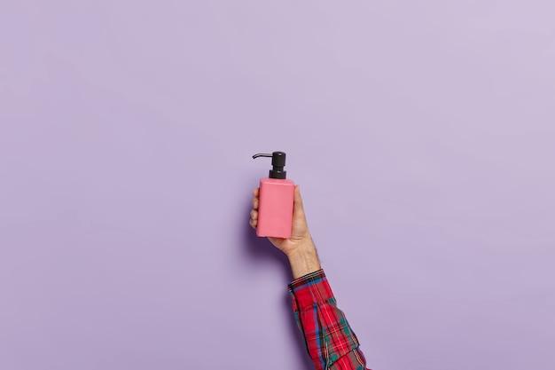 Zdjęcie męskiej dłoni z butelką z rozpylaczem antybakteryjnego mydła w płynie