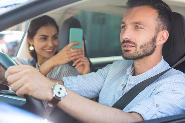 Zdjęcie męża. kochająca piękna żona robi zdjęcie swojego przystojnego brodatego męża prowadzącego samochód
