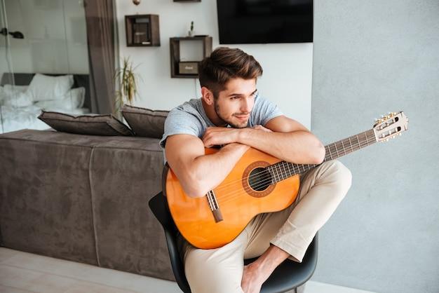 Zdjęcie mężczyzny attracrive siedzącego z gitarą na krześle i spojrzeć na bok.