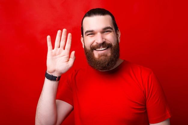 Zdjęcie mężczyzny machającego do aparatu i uśmiechającego się na powitanie