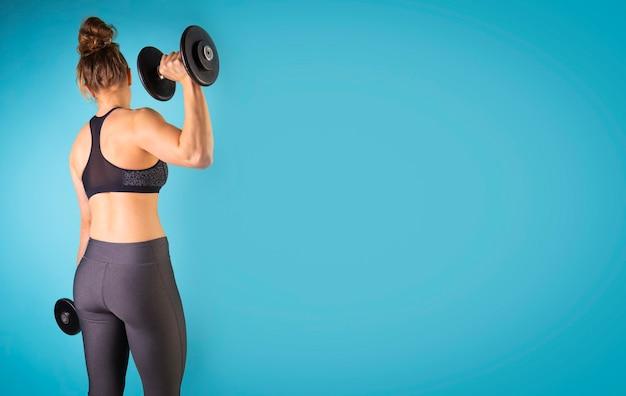 Zdjęcie mięśniowego modelu fitness ćwiczącego z hantlami na niebieskim tle wolne miejsce na kopię