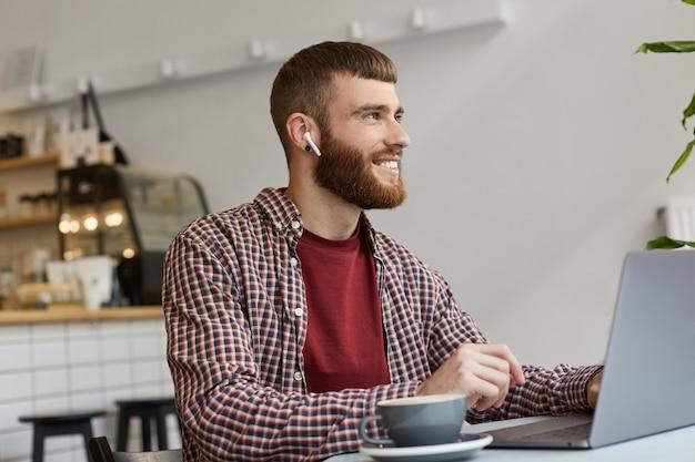 Zdjęcie młodego atrakcyjnego brodacza imbirowego mężczyzny pracującego przy laptopie siedząc w kawiarni, pijąc kawę, nosząc podstawowe ubrania, szeroko uśmiechając się i ciesząc się pracą, odwracając wzrok i uśmiechając się.