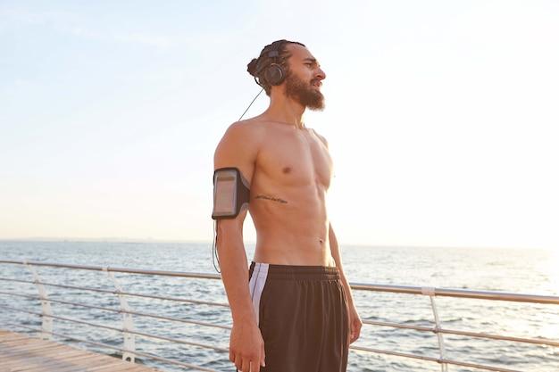 Zdjęcie młodego atrakcyjnego brodatego młodzieńca odpoczynek po joggingu nad morzem, słuchanie ulubionej muzyki na słuchawkach, ciesz się świeżym porankiem.
