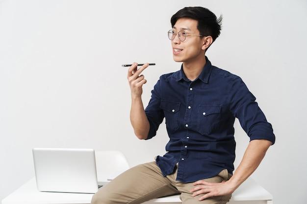 Zdjęcie młodego biznesmena azjatyckiego w okularach, siedzącego przy stole i rozmawiającego na smartfonie podczas pracy z laptopem w biurze na białym tle nad białą ścianą