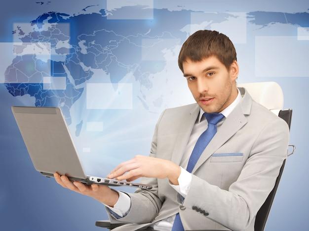 Zdjęcie młodego biznesmena siedzącego na krześle z laptopem
