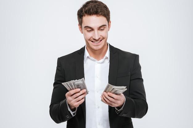 Zdjęcie młodego biznesmena szczęśliwy stojący trzyma pieniądze w rękach. pojedynczo na białej ścianie. spójrz na pieniądze.