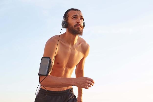 Zdjęcie młodego brodatego mężczyzny biegnącego nad morzem, odwracającego wzrok i słuchającego ulubionych piosenek na słuchawkach.