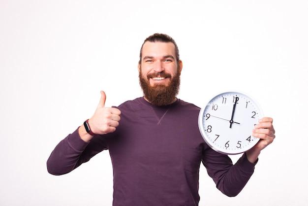 Zdjęcie młodego brodatego mężczyzny trzymającego duży biały zegar i pokazuje kciuk z uśmiechem