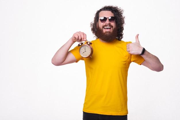 Zdjęcie młodego brodatego mężczyzny z uśmiechniętymi okularami słonecznymi pokazuje kciuk do góry i trzyma mały zegar