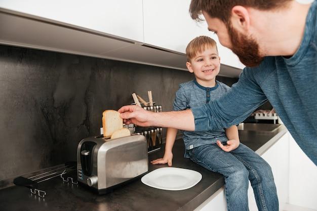 Zdjęcie młodego brodatego ojca ubranego w niebieski sweter gotującego w kuchni ze swoim małym słodkim synkiem