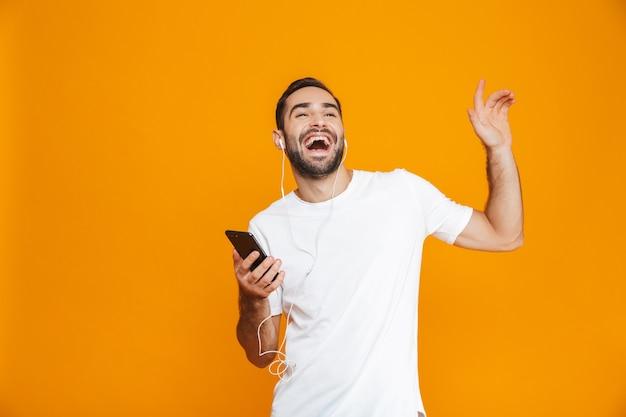 Zdjęcie młodego człowieka 30s słuchanie muzyki za pomocą słuchawek i telefonu komórkowego, na białym tle